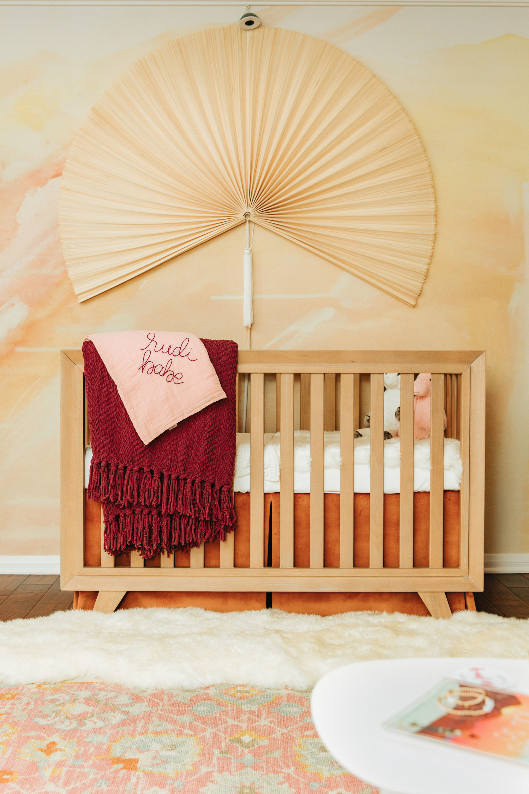 Fan Over Natural Wooster Crib with Abstract Sunrise Wallpaper