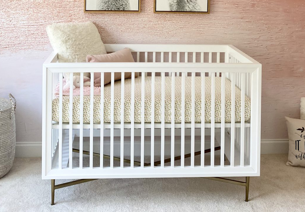 Campaign Crib with Dark Brass Legs and Pink Ombre Nursery Wallpaper