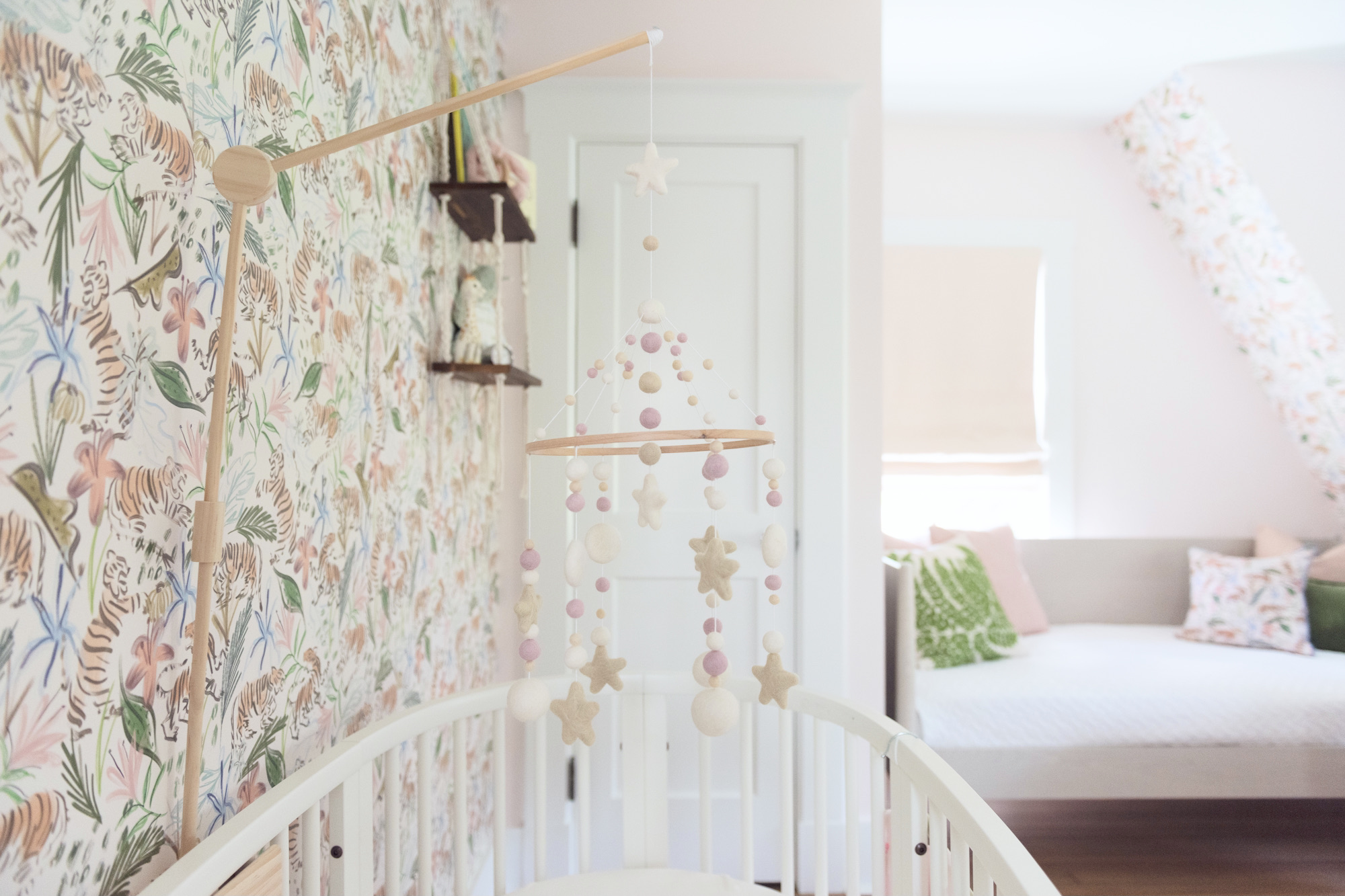 Felted Mobile in Girl's Nursery featuring pink safari wallpaper
